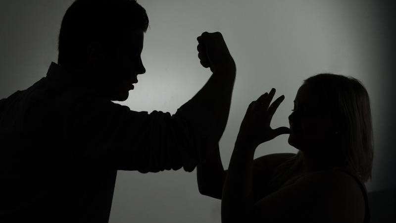 Ein als Silhouette abgebildeter Mann droht einer Frau mit der Faust. Foto: Jan-Philipp Strobel/dpa/Symbolbild