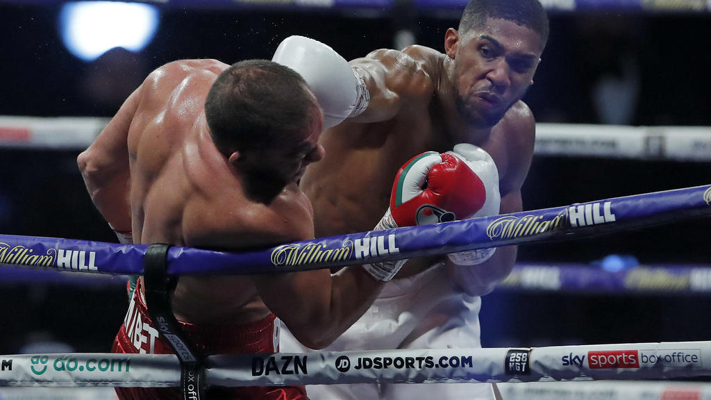World Heavyweight boxing champion Britain's Anthony Joshua lands a blow on challenger Bulgaria's Kubrat Pulev during their Heavyweight title fight at Wembley Arena in London Saturday, Dec. 12, 2020. (Andrew Couldridge/Pool via AP)
