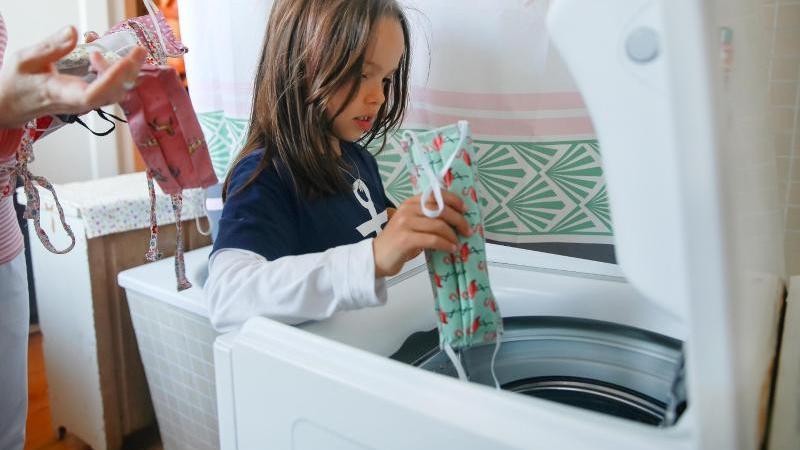 Ab in die Maschine! Alltagsmasken sollten bei mindestens 60 Grad gewaschen werden. Foto: Mascha Brichta/dpa-tmn