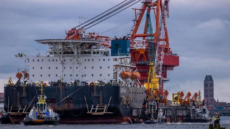 """Schlepper ziehen das russische Rohr-Verlegeschiff """"Fortuna"""" aus dem Hafen auf die Ostsee. Foto: Jens Büttner/dpa-Zentralbild/ZB"""