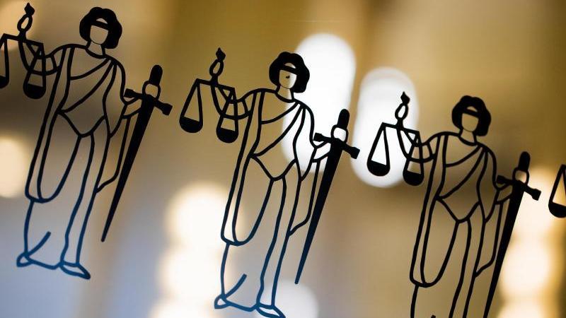 Mehrere Justitia-Abbildungen sind an einer Scheibe zu sehen. Foto: Rolf Vennenbernd/dpa/Archivbild
