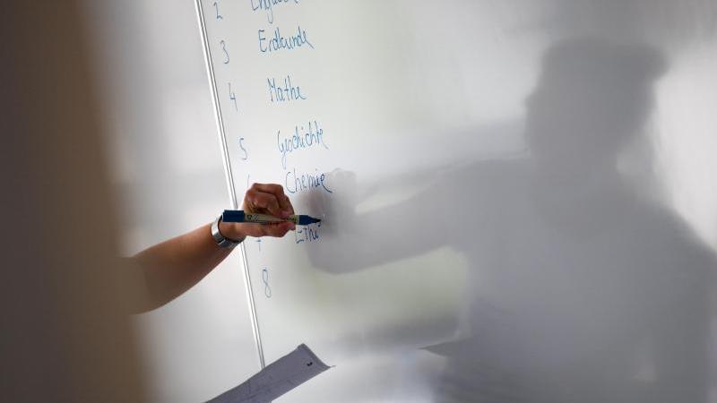 Eine Lehrerin eines Privatgymnasiums schreibt zu Unterrichtsbeginn den Stundenplan an die Tafel. Foto: Arne Dedert/dpa/Archivbild