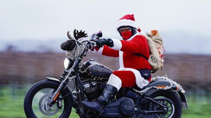 """Patrick Kuntz, Gründer der Initiative """"Harley Davidson riding Santas"""", fährt als Weihnachtsmann verkleidet auf seinem Motorrad. Foto: Uwe Anspach/dpa/Archivbild"""