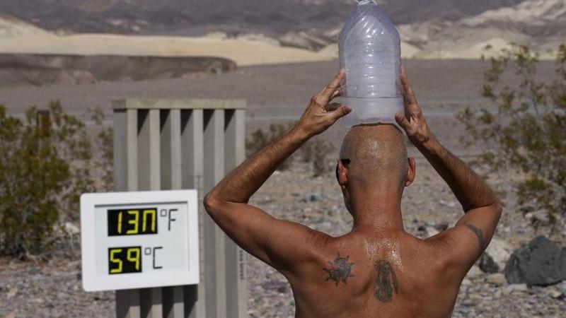 """Ganz schön heiß:Ein Mann kühlt sich im """"Death Valley""""-Nationalpark im US-Bundesstaat Arizona mit einer mit Eiswasser gefüllten Plastikflasche auf dem Kopf ab. Foto: John Locher/AP/dpa"""