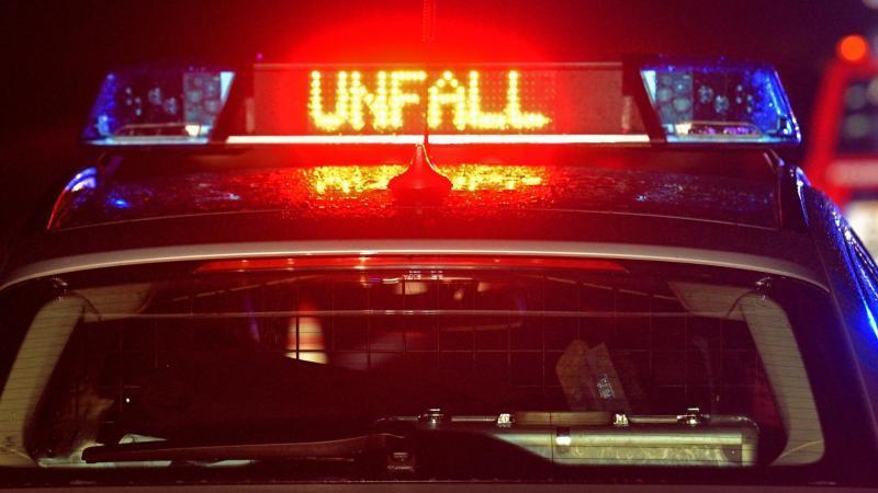 """Blaulicht und der LED- Schriftzug """"Unfall"""" leuchten auf dem nassen Dach eines Polizestreifenwagens. Foto: Stefan Puchner/dpa/Archiv"""