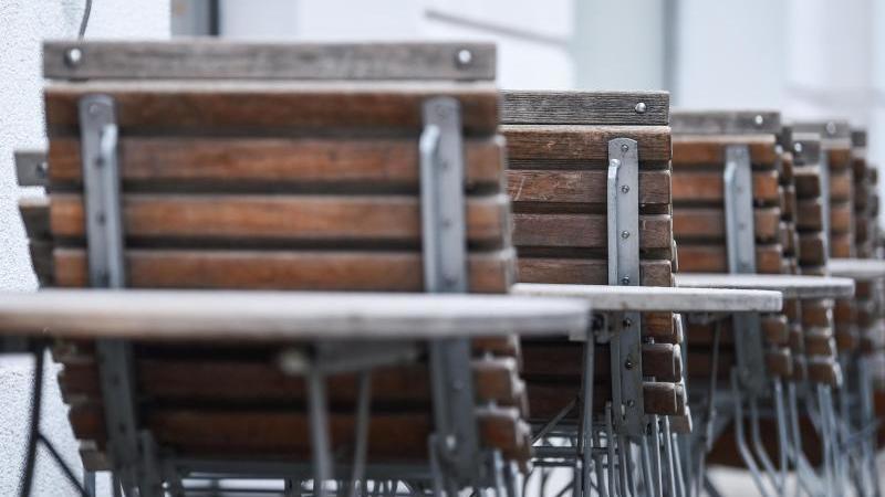 An einem Restaurant stehen zusammengeklappte Stühle. Foto: Kira Hofmann/dpa-Zentralbild/dpa/Archiv
