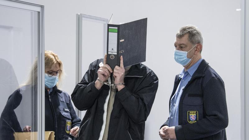 Mit Handschellen wird der Angeklagte (M)in einen provisorischen Verhandlungssaal vom Landgericht Wiesbaden geführt. Foto: Boris Roessler/dpa