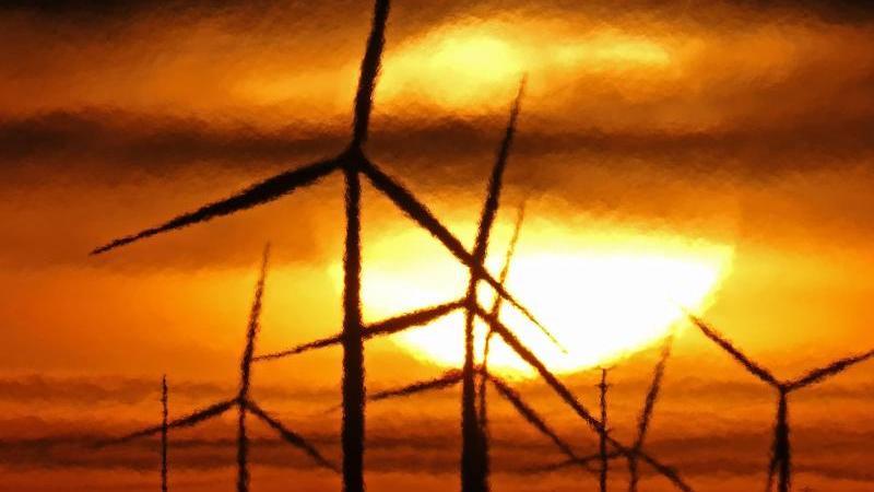 Sonnenaufgang hinter Windrädern. Foto: Charlie Riedel/AP/dpa/Symbolbild/Archiv