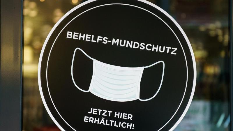 Ein Geschäft wirbt mit einem Behelfs-Mundschutz. Foto: Andreas Arnold/dpa/Symbolbild/Archiv