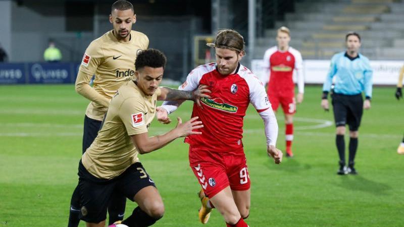Der Freiburger Lucas Höler (M.) im Zweikampf mit dem Frankfurter Tuta. Foto: Philipp von Ditfurth/dpa