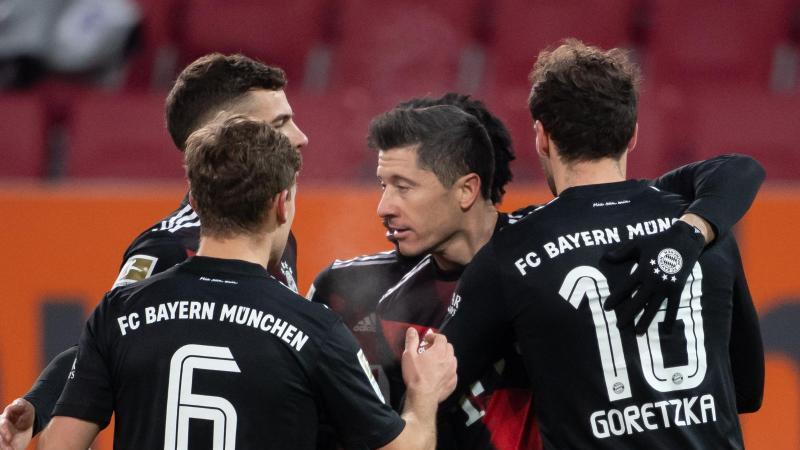 Der FC Bayern München setzte sich auch dank Torjäger Robert Lewandowski (M.) knapp in Augsburg durch. Foto: Sven Hoppe/dpa