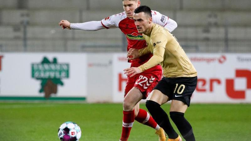 Roland Sallai (l) vom SC Freiburg und Filip Kostic von Eintracht Frankfurt in Aktion. Foto: Philipp von Ditfurth/dpa