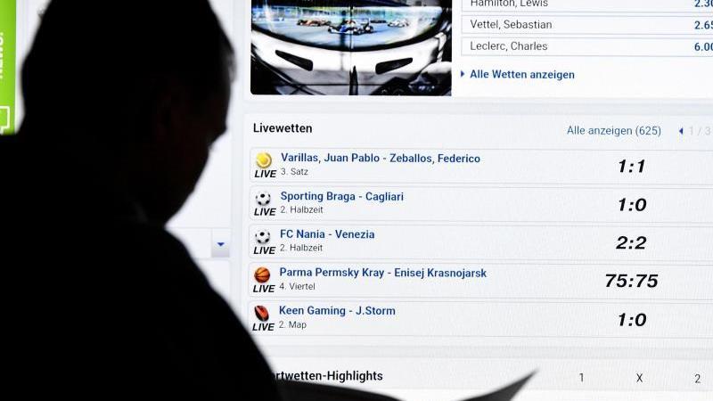 Ein Mann steht vor einem Bildschirm mit der Seite eines Anbieters für Sportwetten. Foto: Carsten Rehder/dpa/Illustration