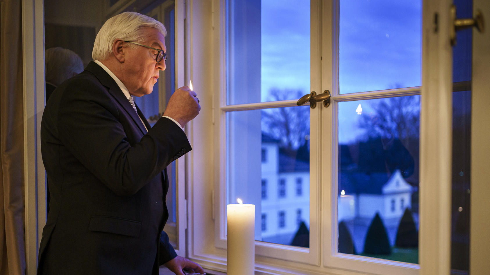 Das am 22.01.2021 zur Verfügung gestellte Foto zeigt Bundespräsident Frank-Walter Steinmeier, der mit einem Licht in einem Fenster von Schloss Bellevue ein Zeichen des gemeinsamen Gedenkens setzt und zur Aktion #lichtfenster aufruft. | Handout