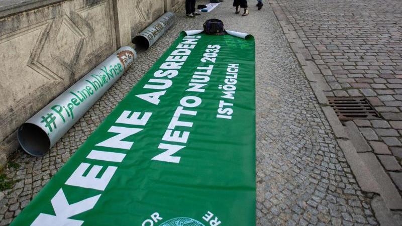 Mitglieder der Bewegung Fridays for Future protestieren mit einer symbolischen Rohrleitung vor den Landtagssitz im Schweriner Schloss gegen den Weiterbau der Gaspipeline Nord Stream 2. Foto: Jens Büttner/dpa-Zentralbild/dpa/Archivbild