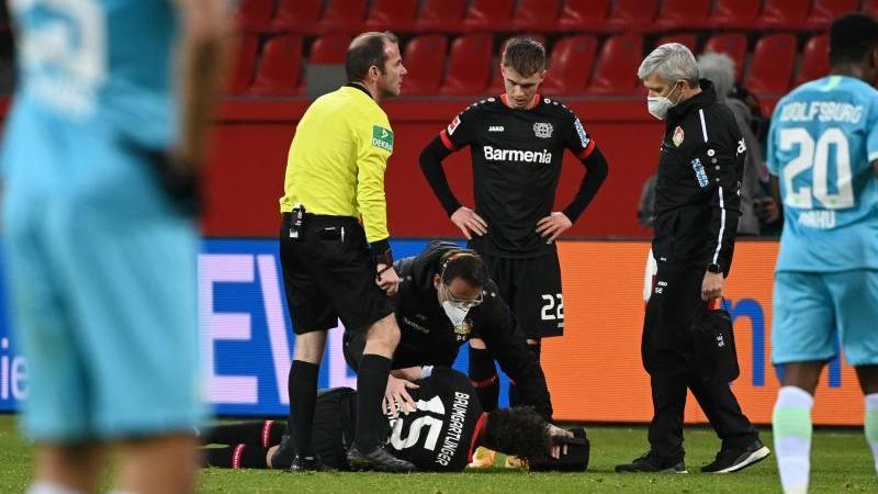 Leverkusens Julian Baumgartlinger beim Spiel gegen Wolfsburg auf dem Boden und wird behandelt. Foto: Ina Fassbender/AFP/Pool/dpa