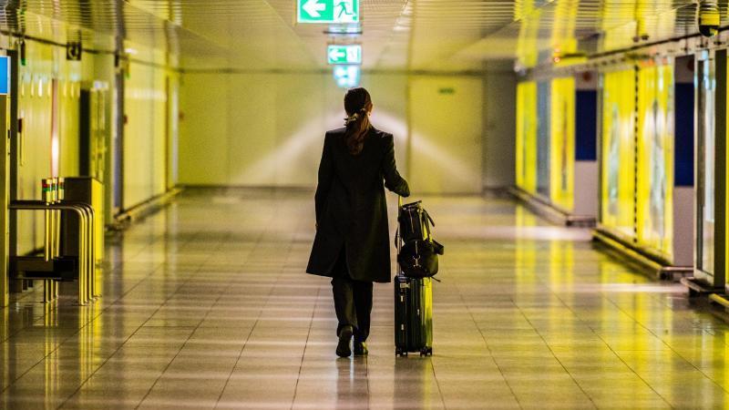 Eine Frau geht mit ihrem Koffer durch einen leeren Gang auf dem Flughafen Frankfurt. Foto: Andreas Arnold/dpa/Archivbild
