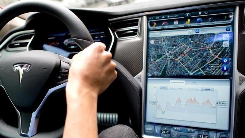 Ein Mann sitzt in einem Tesla Model S amLenkrad, neben ihm ein großer Monitor imArmaturenbrett. Foto: picture alliance / dpa