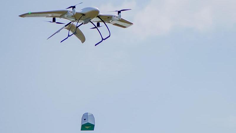 Eine Drohne des Start-Ups Wingcopter trägt ein Paket. Das mit Tragflächen ausgestattete Gerät kann senkrecht aufsteigen und dann auf der Strecke auch bei widrigen Wetterverhältnissen wie ein Propeller-Flugzeug fliegen. Foto: Wingcopter/dpa
