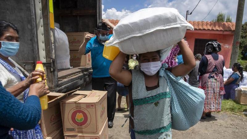 Eine Frau mit Mundschutz macht sich in San Jose Calderas, Guatemala, mit einem Sack voll Hilfsgütern auf den Heimweg. Foto: Moises Castillo/AP/dpa