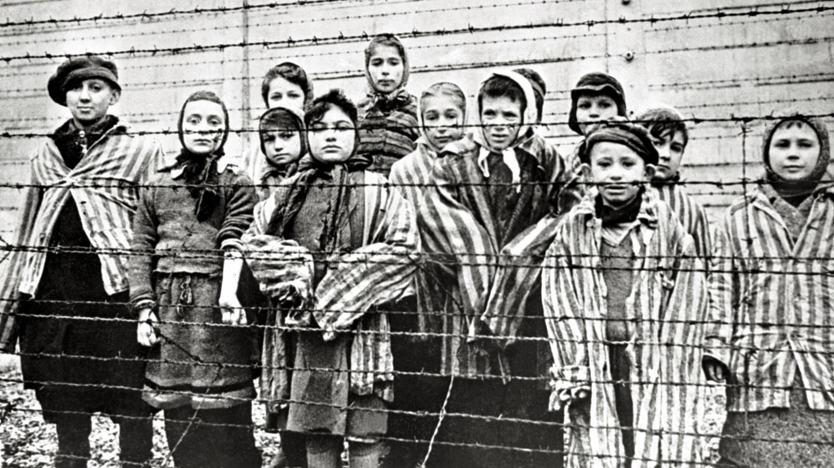 Überlebende jüdische Kinder in Auschwitz Mit Krankenschwester hinter Stacheldrahtzaun. Das Foto wurde von einem sowjeti