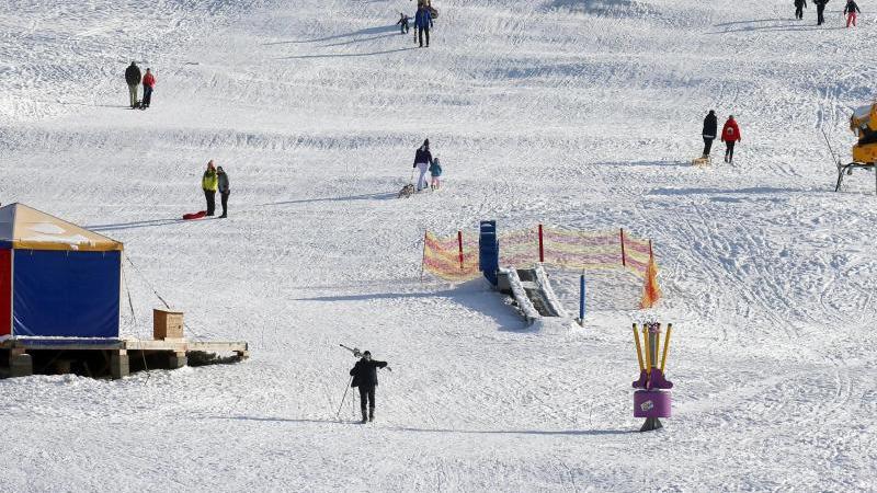 Ausflügler mit Schlitten und Ski vergnügen sich auf einer Piste im Sonnenschein. Foto: Karl-Josef Hildenbrand/dpa/Archivbild
