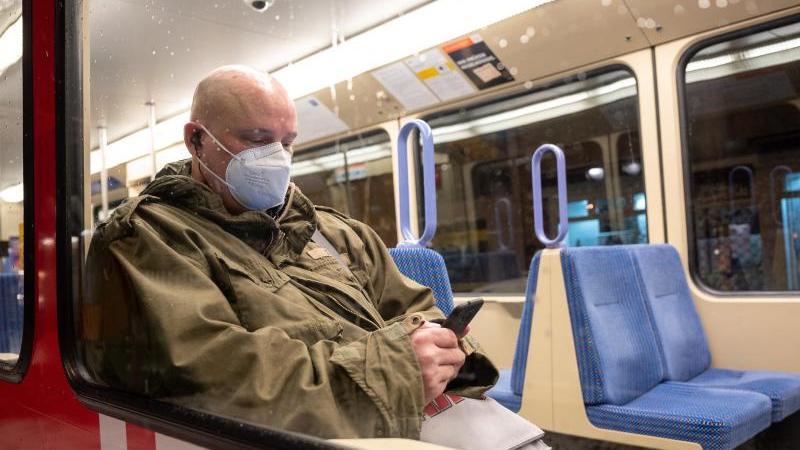 Ein Mann sitzt mit einer FFP2-Maske in einer U-Bahn. Foto: Sebastian Gollnow/dpa/Archivbild