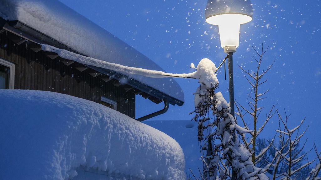 Eine Strassenlaterne leuchtet an einem Wintermorgen bei Schneefall zur blauen Stunde in Leutkirch in Baden Württemberg