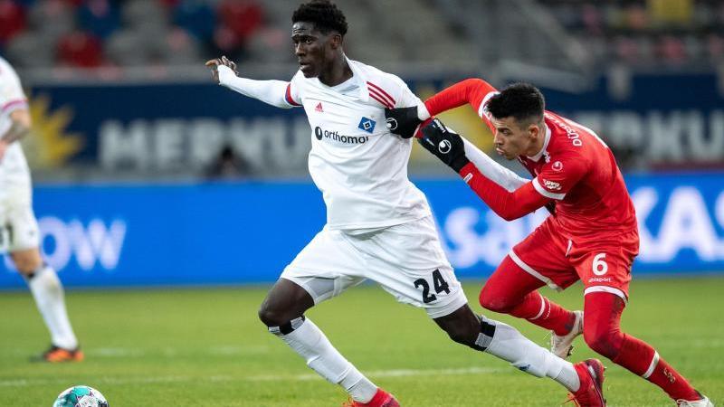 Hamburgs Amadou Onana (l) kämpft gegen Düsseldorfs Alfredo Moraes um den Ball. Foto: Marius Becker/dpa