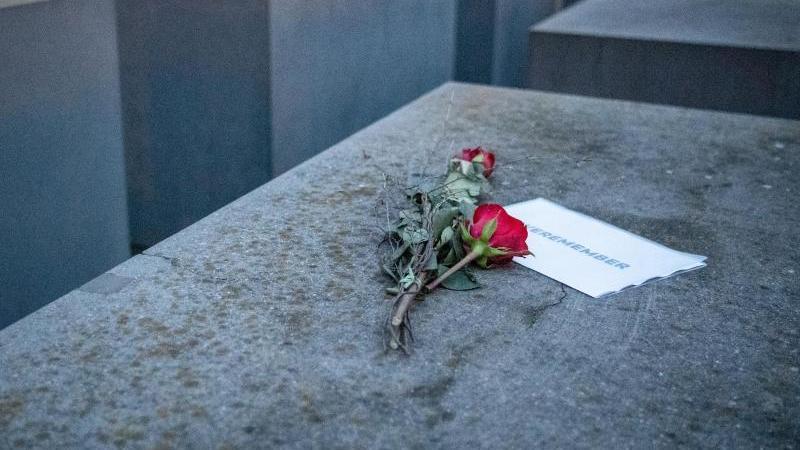 """Rosen liegen mit einem Zettel, mit der Aufschrift """"#weremeber"""" am Holocaust-Mahnmal in Berlin. Foto: Dorothee Barth/dpa"""