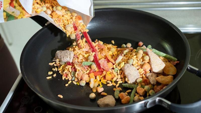 """Zubereitung des Fertiggerichtes """"Hähnchen Paella"""" in einer Pfanne. Foto: Peter Steffen/dpa/Symbol"""