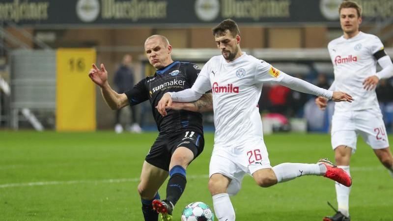 Sven Michel (l-r) vom SC Paderborn und Jonas Meffert von Holstein Kiel kämpfen um den Ball. Foto: Friso Gentsch/dpa