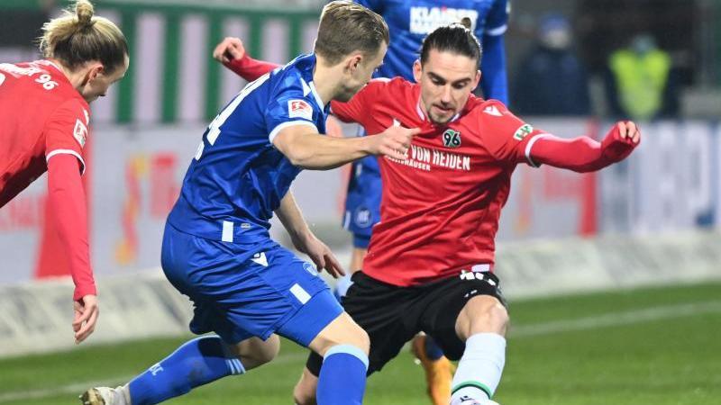 Karlsruhes Marco Thiede (l) und Valmir Sulejmani von Hannover 96 kämpfen um den Ball. Foto: Uli Deck/dpa