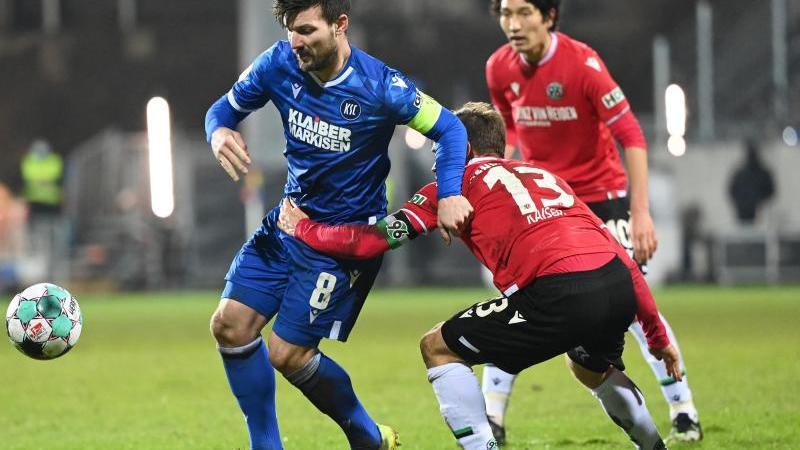 Jerôme Gondorf (l) vom Karlsruher SC und Dominik Kaiser von Hannover 96 kämpfen um den Ball. Foto: Uli Deck/dpa