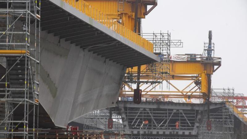 Arbeiter stehen im Inneren eines Bogens der Schiersteiner Brücke an einem Seitenarm des Rheins. Foto: Boris Roessler/dpa