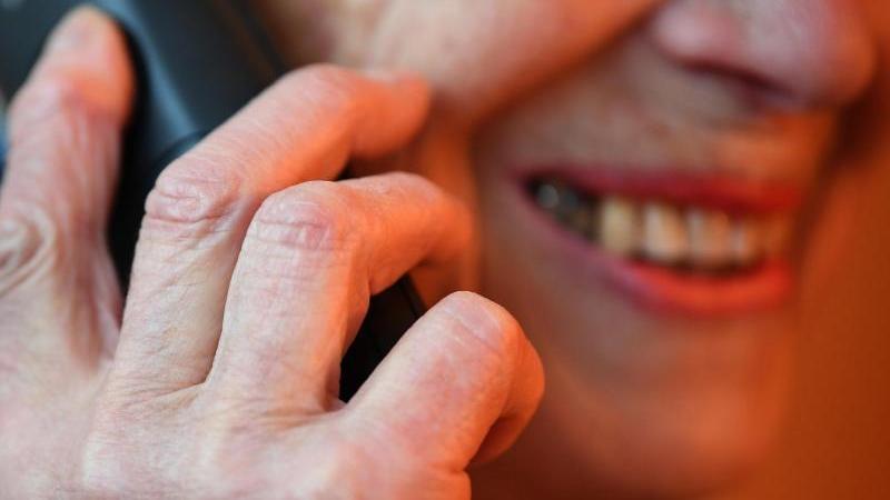 Eine Seniorin hält einen Telefonhörer an ihr Ohr und lächelt (gestellte Szene). Foto: Britta Pedersen/dpa-Zentralbild/dpa/Archivbild