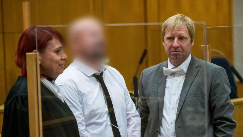 Der Mitangeklagte Markus H. (M) steht zwischen seiner Anwältin Nicole Schneiders und seinem Anwalt Björn Clemens in einem Gerichtssaal des Oberlandesgerichts. Foto: Thomas Lohnes/AFP POOL/dpa/Aktuell