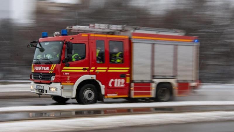 Ein Feuerwehrwagen fährt mit Blaulicht zu einem Einsatzort. Foto: Peter Kneffel/dpa/Symbolbild