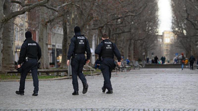 Polizisten laufen über eine Straße um die Einhaltung der Corona-Schutzverordnung zu kontrollieren. Foto: Robert Michael/dpa-Zentralbild/dpa/Archivbild