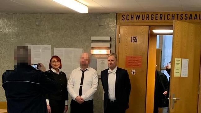 Markus H. macht direkt nach dem Urteil im Lübcke-Prozess Fotos mit seinen beiden Verteidigern - fotografiert von einem Justizbeamten.