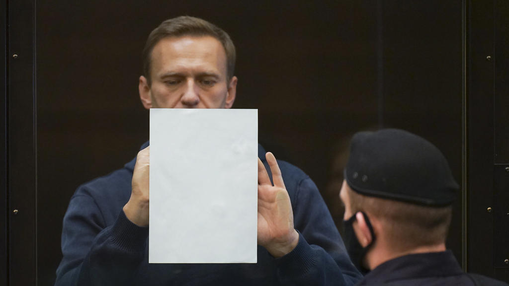 HANDOUT - 02.02.2021, Russland, Moskau: In diesem Handout-Foto, das vom Moskauer Stadtgericht zur Verfügung gestellt wurde, hält der russische Oppositionsführer Alexej Nawalny ein Dokument im Käfig stehend bei einer Anhörung zu einem Antrag des russi