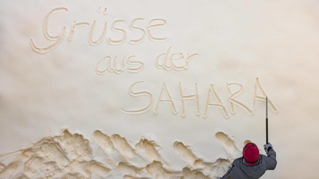Blutschnee mit Sandstaub aus der Sahara Eine Frau schreibt Grüße aus der Sahara in den Schnee. Der gelb-orange Sandstaub aus der Sahara ist für den Blutschnee - Effekt verantwortlich. Ilmenau Thüringen DEUTSCHLAND *** Blood snow with sand dust from