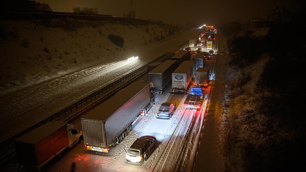 08.02.2021, Sachsen, Dresden: Autos und Lastwagen stehen am frühen Morgen bei Schneefall auf der verschneiten Autobahn 4 bei Dresden im Stau, während ein Mann neben seinem Auto steht. Foto: Robert Michael/dpa-Zentralbild/dpa +++ dpa-Bildfunk +++