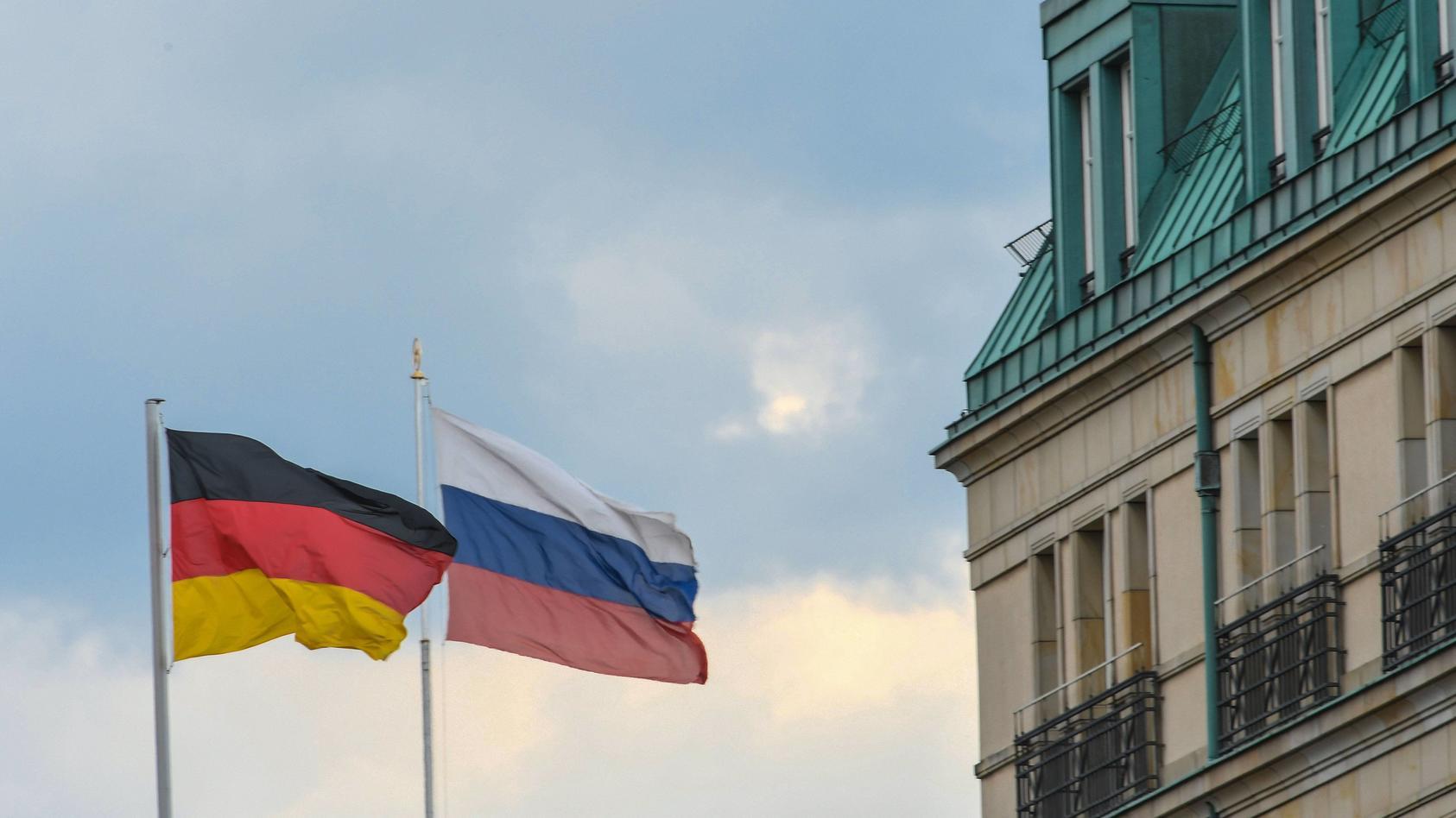 Die deutsche und die russische Fahne wehen in Berlin nahe der Botschaft der russischen Föderation