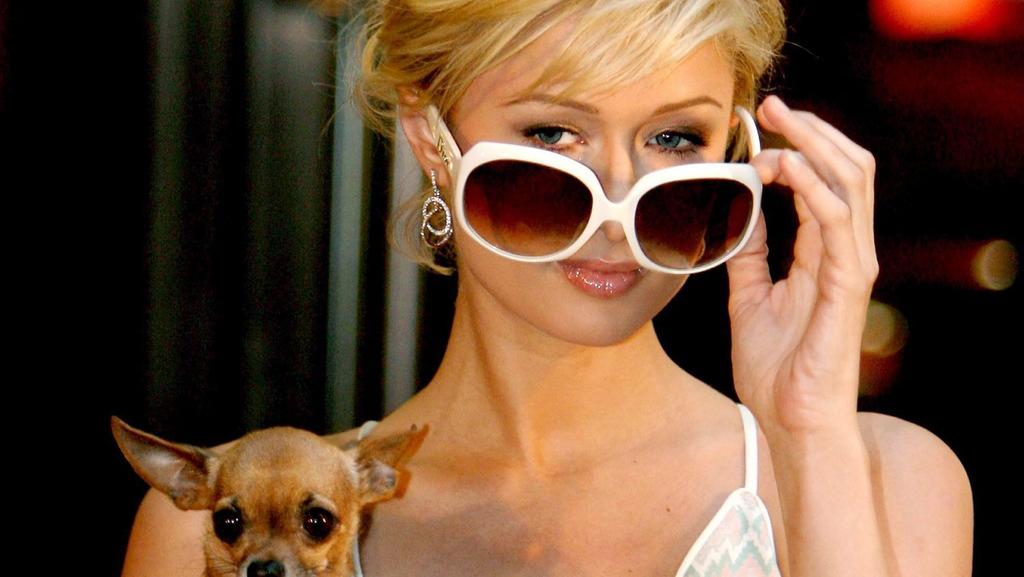 ARCHIV - 30.11.2005, USA, New York: Paris Hilton trägt ihren Hund Tinkerbell bei einer Veranstaltung in New York auf dem Arm. Das Ex-It-Girl feiert am 17.02.2021 ihren 40. Geburtstag. (zu dpa: «Ex-It-Girl der Nation - Paris Hilton wird 40») Foto: Jus