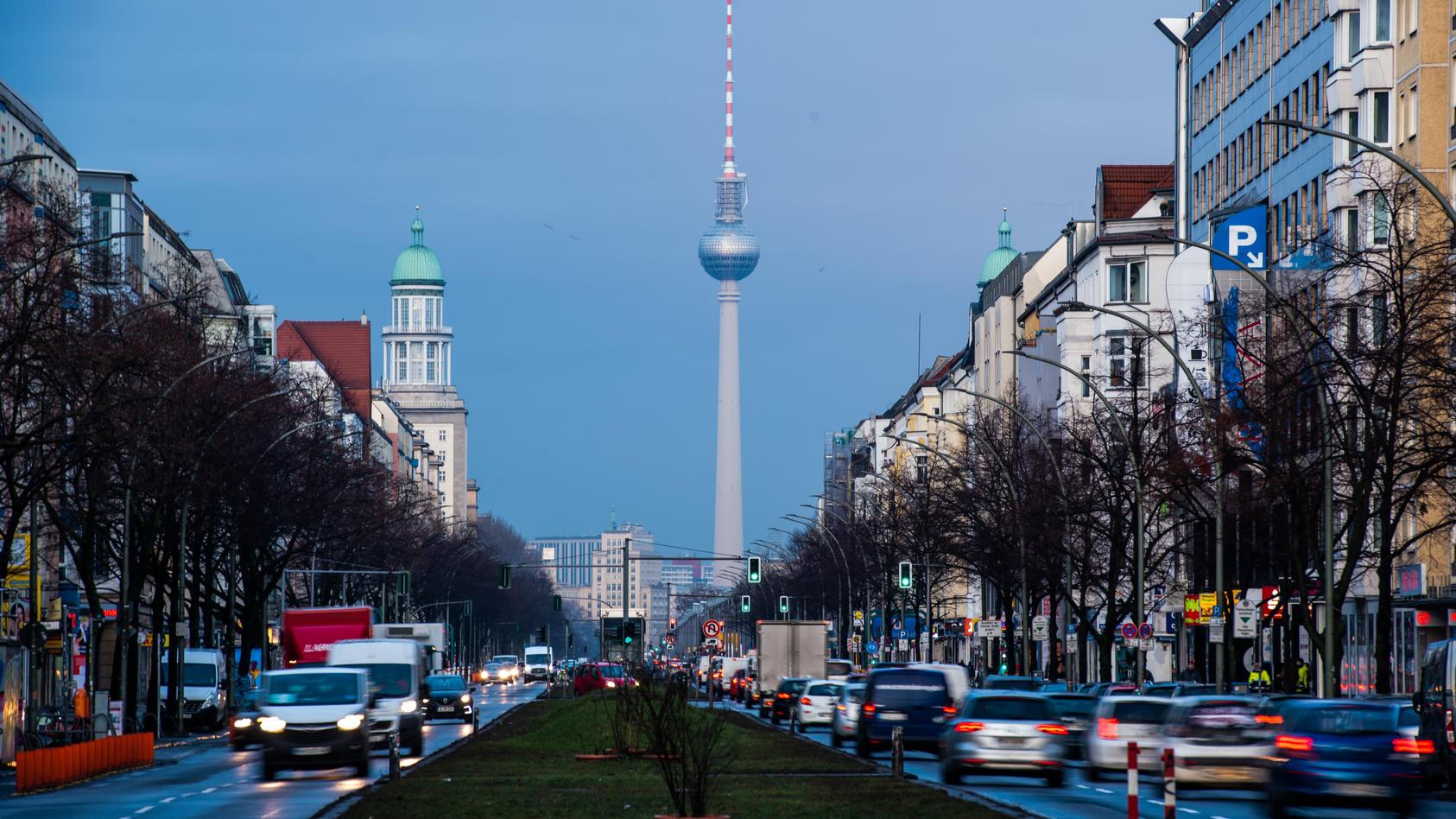Autos fahren in Berlin auf der Frankfurter Allee im morgendlichen Berufsverkehr. Im Hintergrund ist dabei der Fernsehturm zu sehen.