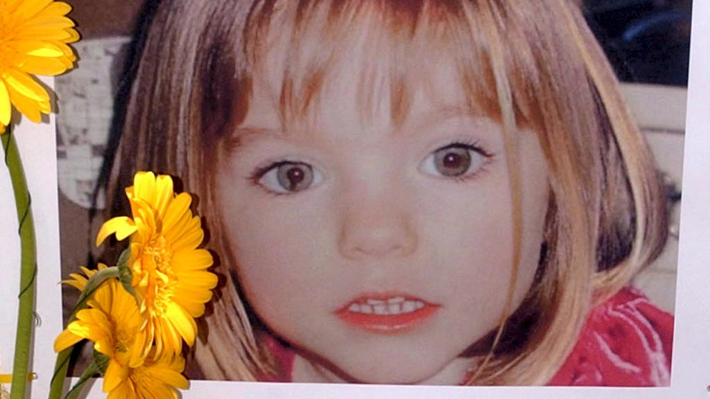 """ARCHIV - 12.05.2007, Portugal, Lagos: Blumen stehen vor einem Bild, das die verschwundenenMadeleine McCann (Maddie) auf einem Foto zeigt, das ihre Eltern im Zusammenhang mit dem Verschwinden des Kindes veröffentlich haben. (zu dpa: """"Fall Maddie: Erm"""