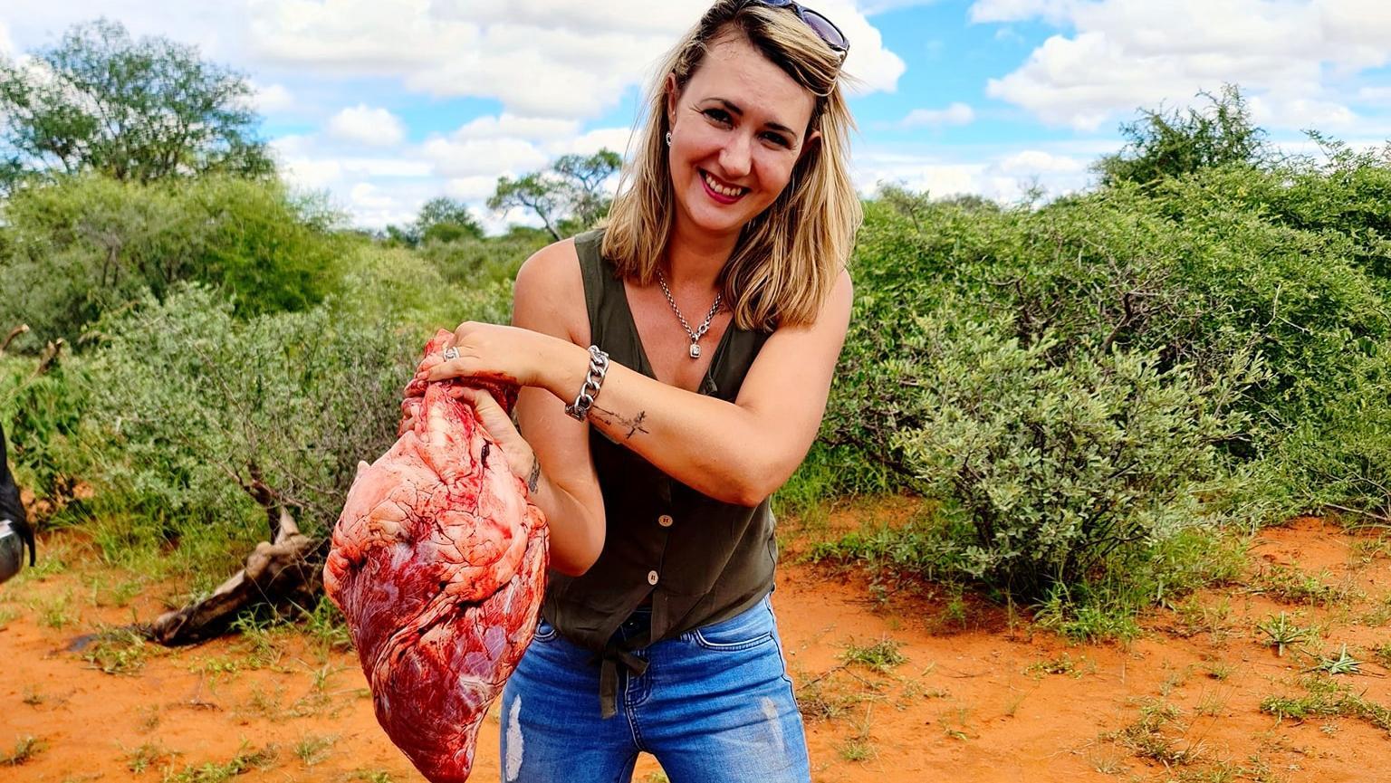 Merelize van der Merwe posiert stolz mit dem Herz einer Giraffe, die sie gerade erschossen hat.