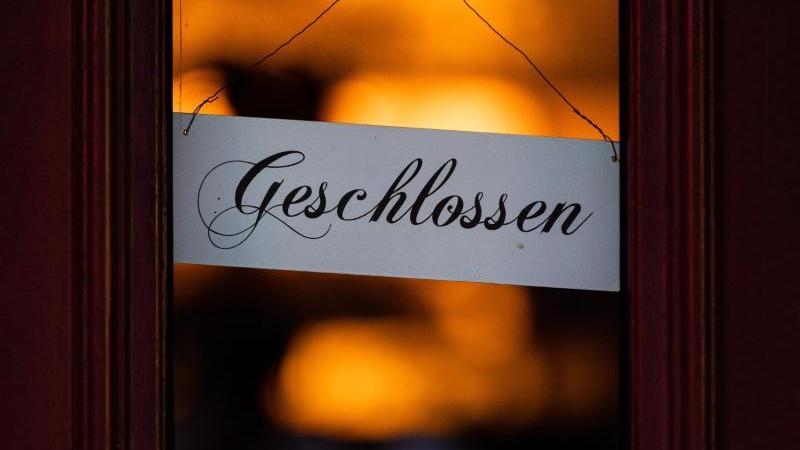 """Ein Schild mit der Aufschrift """"Geschlossen"""" hängt an einer Eingangstür. Foto: Rolf Vennenbernd/dpa/Archivbild"""