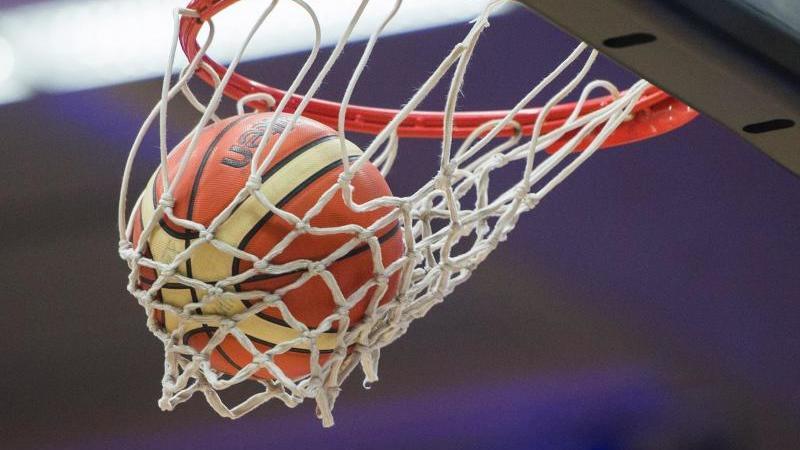 Ein Basketball fällt in den Basketballkorb. Foto: picture alliance / dpa/Symbolbild